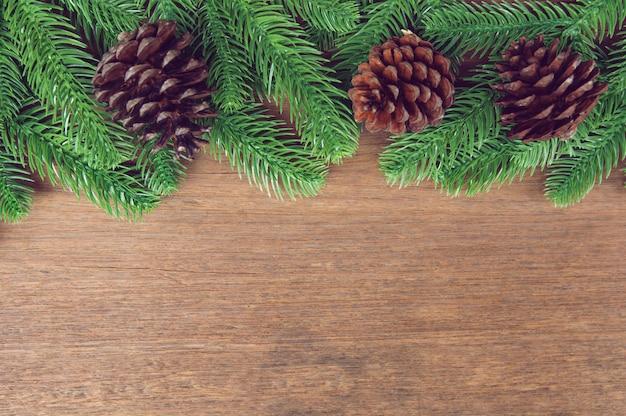 Galhos de árvore do abeto e pinhas com decoração em uma placa de madeira Foto Premium