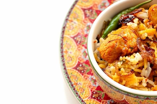 Galinha indiana biryani com fundo do branco do raita do tomate do iogurte. foco seletivo. Foto Premium
