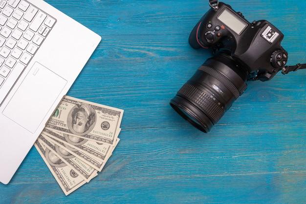 Ganhe dinheiro na câmera dslr da internet, dólares, laptop, sobre fundo azul de madeira, vista superior Foto Premium