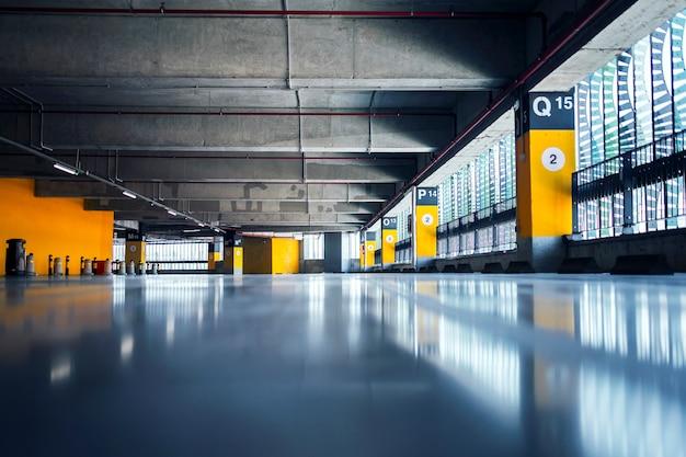 Garagem vazia com estacionamentos com teto e piso de concreto e pilares marcados com números Foto gratuita