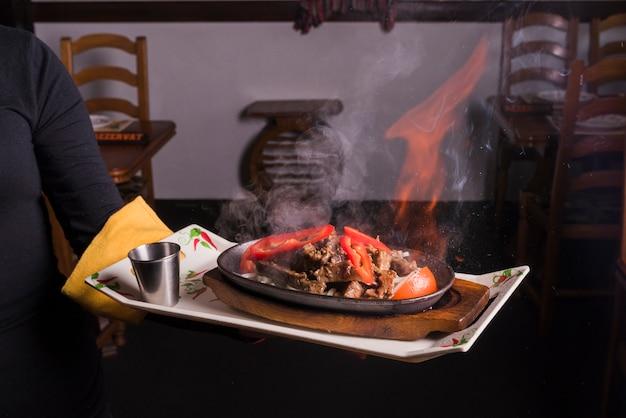Garçom, bandeja levando, com, carne, fogo Foto gratuita
