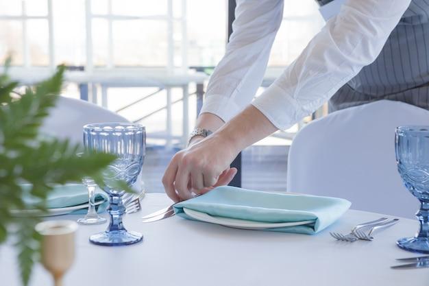 Garçom de restaurante serve uma mesa para uma festa de casamento Foto Premium