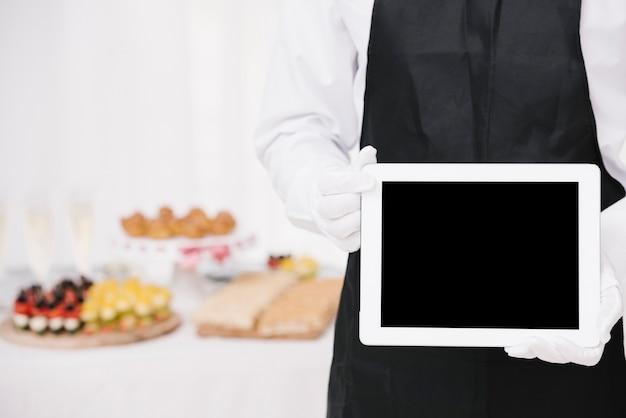 Garçom de uniforme segurando um tablet com mock-up Foto gratuita