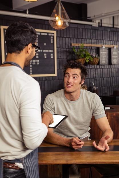 Garçom e cliente falando Foto Premium