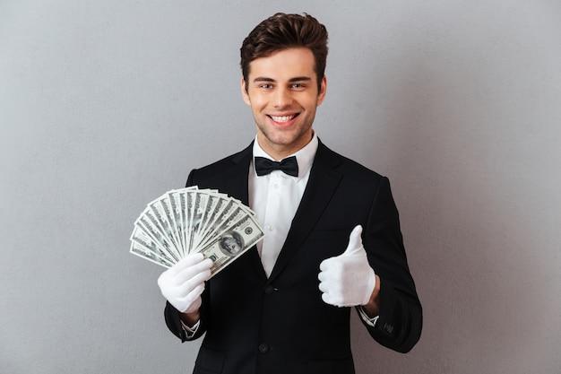 Garçom novo alegre, mostrando os polegares, mantendo o dinheiro. Foto gratuita