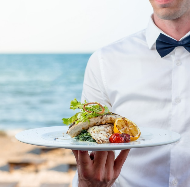 Garçom segurando peixe grelhado com limão, tomate, ervas cremosas no restaurante à beira-mar Foto gratuita
