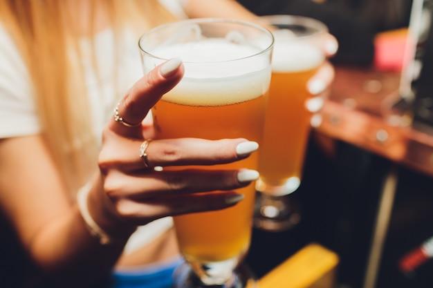 Garçom, servindo copos de cerveja gelada na bandeja Foto Premium