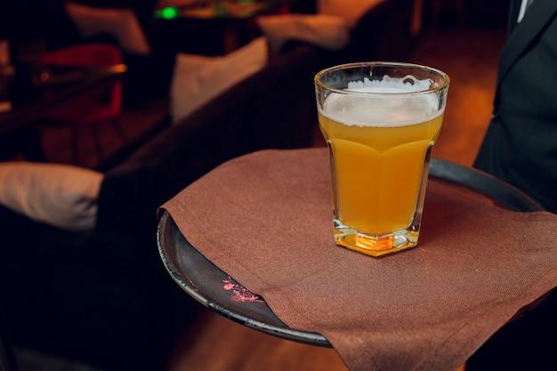 Garçom servindo copos de cerveja gelada na bandeja. Foto Premium