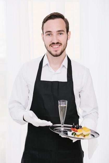 Garçom sorridente, apresentando champanhe Foto gratuita
