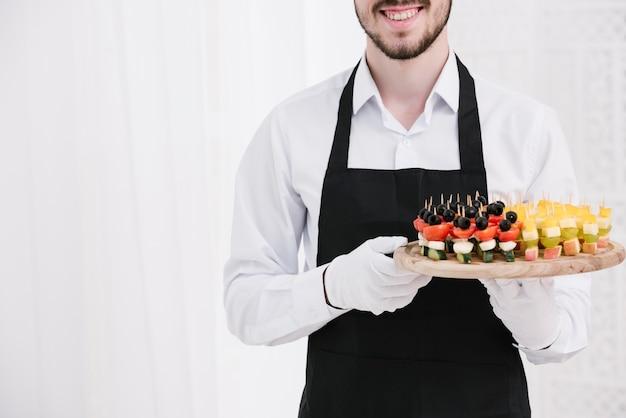 Garçom sorridente segurando lanches em um prato Foto gratuita