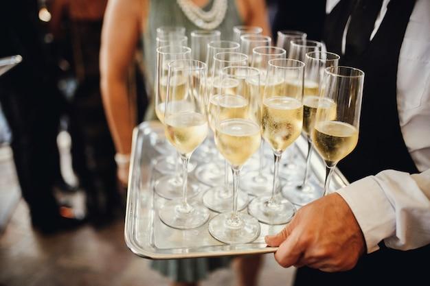 Garçom traz óculos com champanhe gelado Foto gratuita