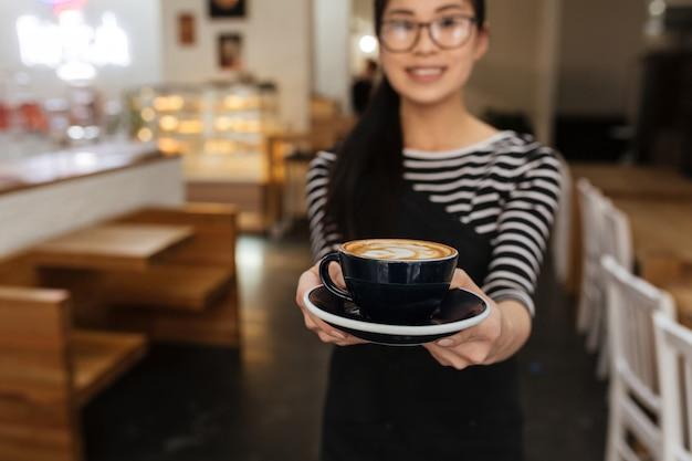 Garçonete asiática estende a xícara de café Foto Premium