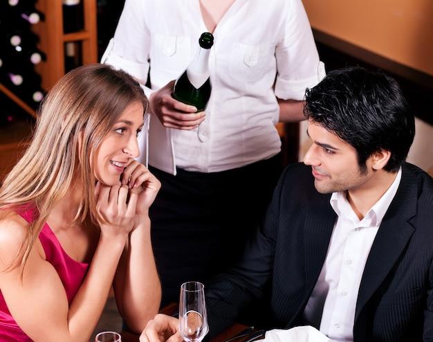 Garçonete, encher copos com champanhe Foto Premium