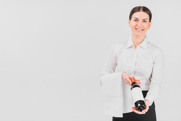 Garçonete mulher oferecendo garrafa de vinho Foto gratuita