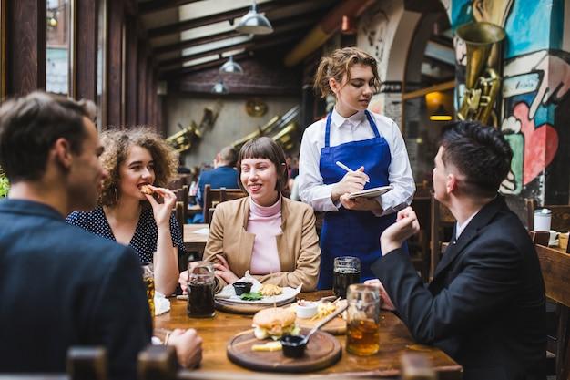 Garçonete recebendo ordens de pessoas no restaurante Foto gratuita