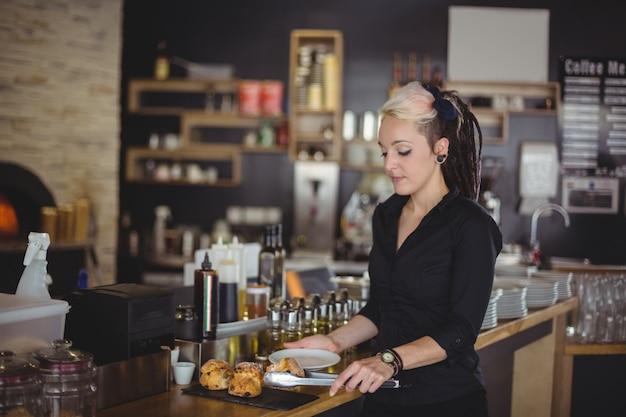 Garçonete, servindo, muffin, em, um, prato, em, contador Foto gratuita