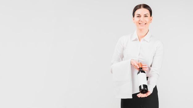 Garçonete, sorrindo, e, holing, garrafa vinho Foto gratuita