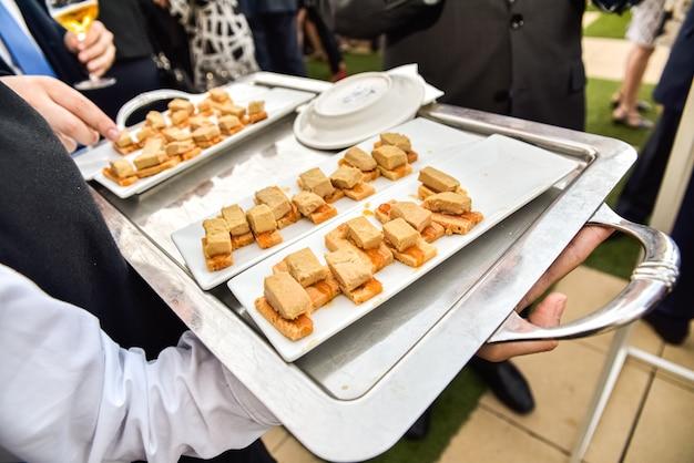 Garçons servindo em bandejas, lanches e tapas para os convidados em um jantar de negócios. Foto Premium