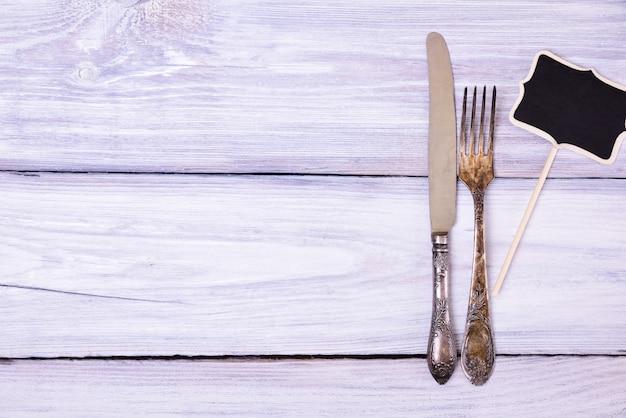 Garfo de ferro e faca em uma superfície de madeira branca Foto Premium