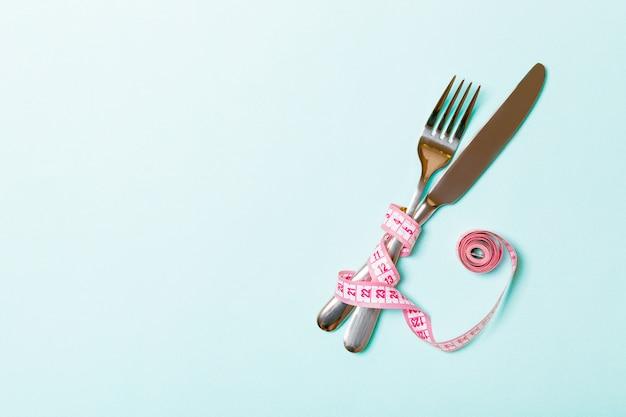 Garfo e faca cruzados são embrulhados em fita métrica Foto Premium