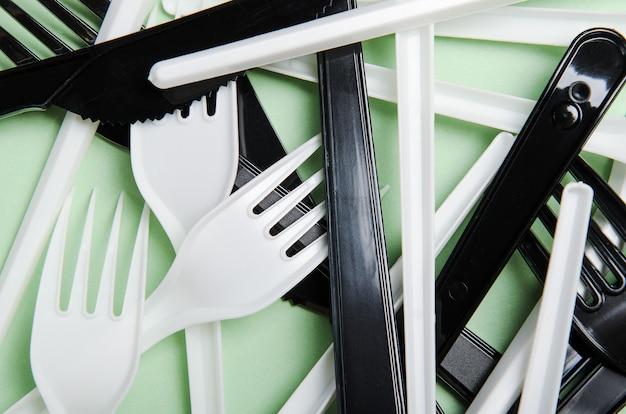 Garfos e facas de plástico brancos e pretos em uma superfície verde Foto Premium