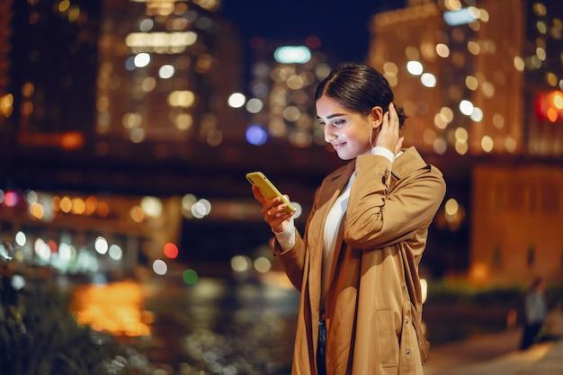 Garota à noite com telefone Foto gratuita