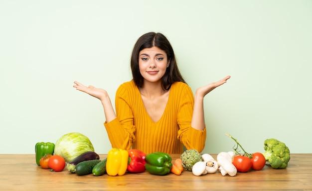 Garota adolescente com muitos vegetais tendo dúvidas ao levantar as mãos Foto Premium