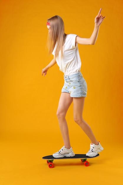 Garota adolescente em pé e posando de skate sobre um fundo de cor Foto Premium