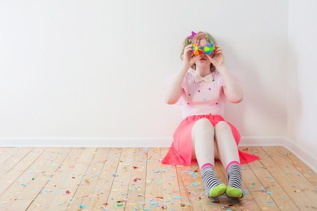 Garota adolescente em traje de palhaço, sentada no chão de madeira Foto Premium