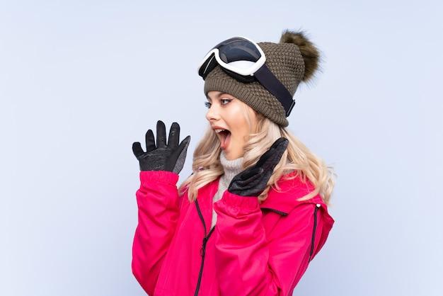 Garota adolescente esquiador com óculos de snowboard sobre fundo azul isolado com expressão facial de surpresa Foto Premium