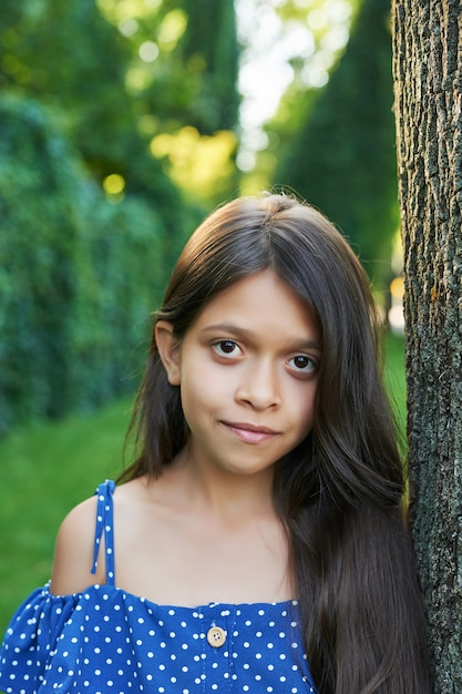 Garota adolescente perto de uma árvore em um parque de verão ao pôr do sol Foto Premium