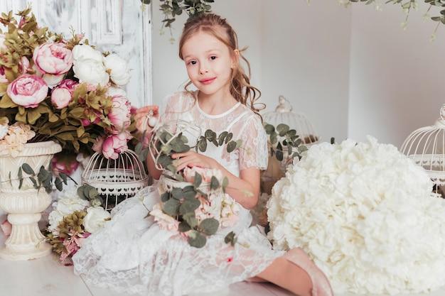 Garota adorável cercada por flores Foto gratuita