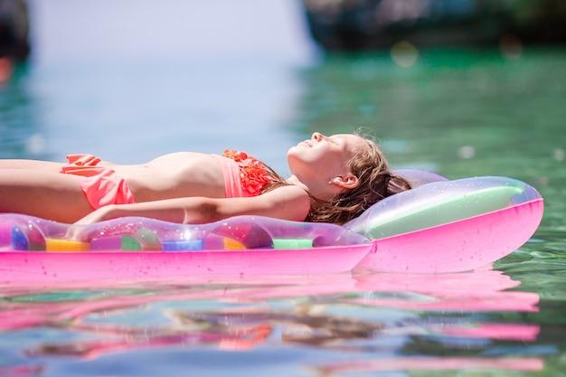 Garota adorável colchão de ar inflável no mar Foto Premium