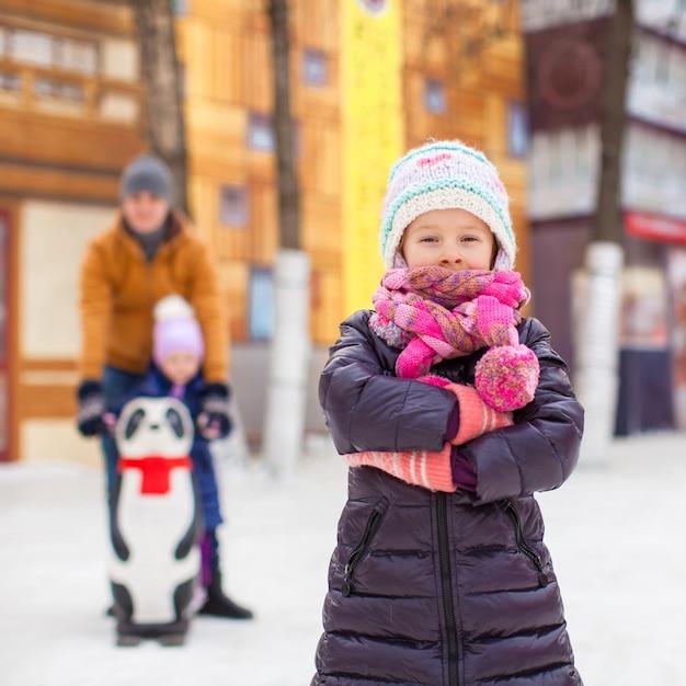 Garota adorável na pista de patinação, pai com irmãzinha Foto Premium
