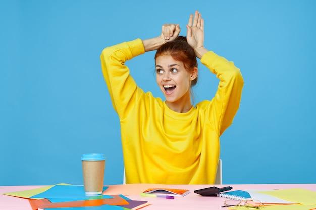 Garota adorável senta-se em uma mesa multicolorida criativa Foto Premium