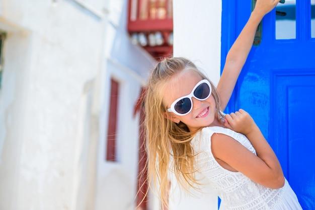 Garota adorável vestido branco ao ar livre em ruas antigas um mykonos. garoto na rua da típica vila tradicional grega, com paredes brancas e portas coloridas na ilha de mykonos, na grécia Foto Premium
