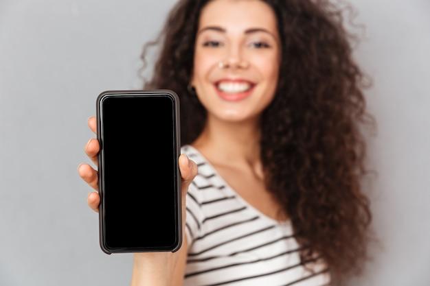 Garota adulta atraente com anel no nariz, demonstrando seu telefone móvel anunciando novo modelo sendo feliz enquanto isolado contra parede cinza Foto gratuita