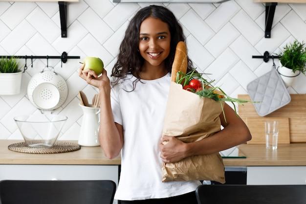 Garota africana fica na cozinha e segura um saco de papel com compras Foto gratuita