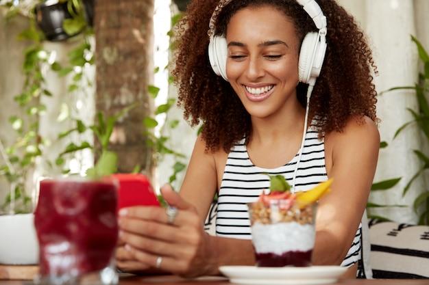 Garota afro-americana hipster positiva busca novas músicas, feliz por receber mensagens no celular. amante de música ouve composição da lista de reprodução e digita sms de texto nas redes sociais Foto gratuita
