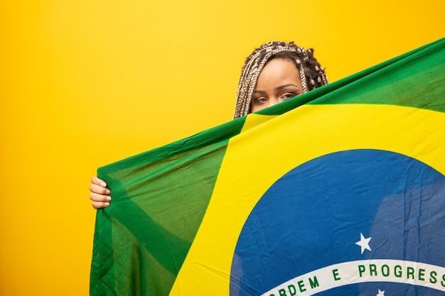 Garota afro torcendo por time brasileiro favorito, segurando a bandeira nacional em amarelo. Foto Premium