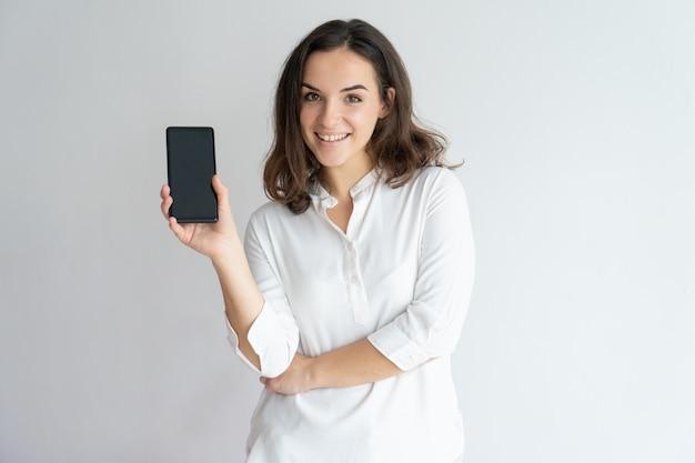 Garota alegre feliz apresentando novo aplicativo na tela do celular. Foto gratuita