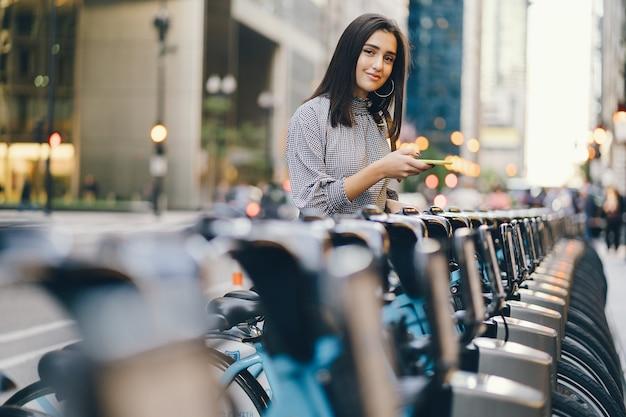 Garota alugando uma bicicleta da cidade de um stand de bicicleta Foto gratuita