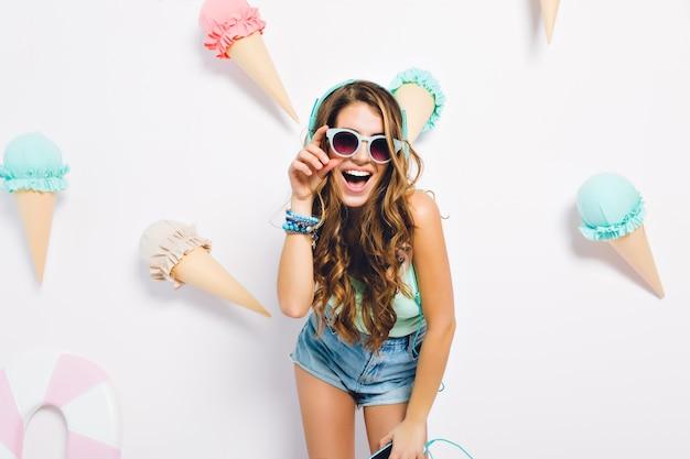 Garota animada com cabelo encaracolado brilhante, posando na parede decorada, usando shorts jeans e óculos escuros. retrato de uma jovem feliz com telefone e fones de ouvido em pé com um sorriso feliz. Foto gratuita