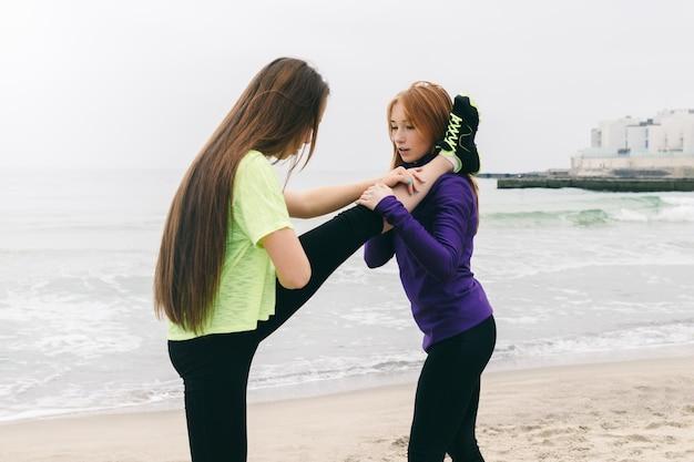 Garota atlética no sportswear ajuda uns aos outros para fazer alongamento na praia em um dia nublado Foto Premium