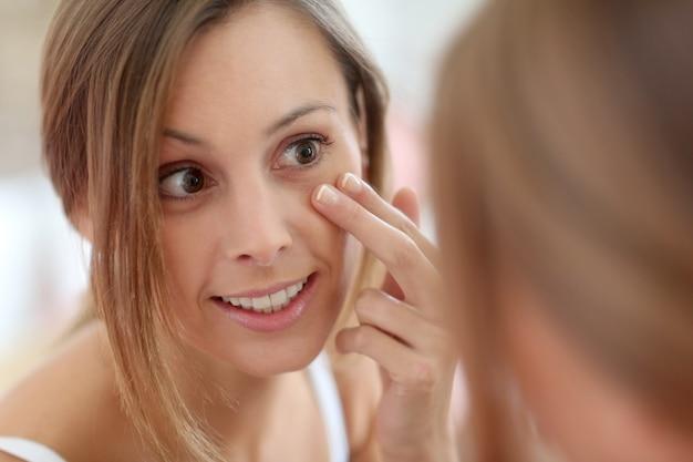 Garota atraente colocando creme anti-envelhecimento no rosto Foto Premium