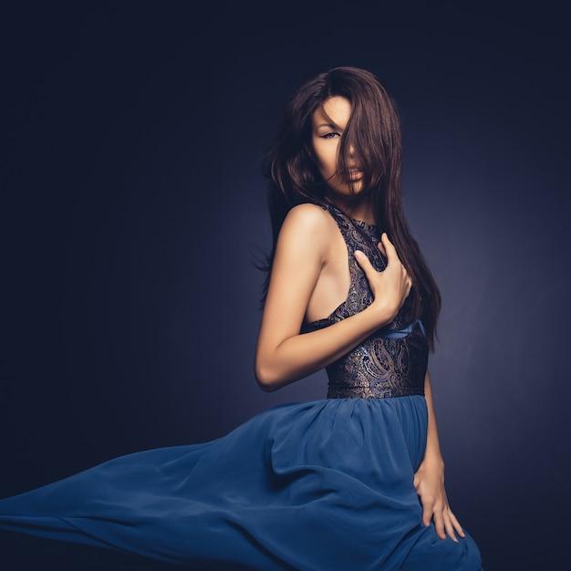 Garota atraente com cabelo a voar posando no estúdio Foto gratuita