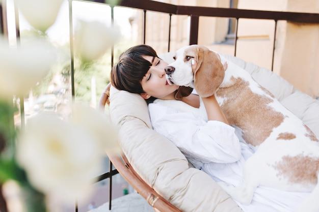 Garota atraente com cabelo curto escuro beijando um cachorro beagle que olha para longe Foto gratuita