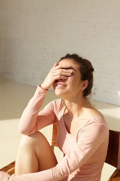 Garota atraente com sorriso fofo cobre o rosto com a mão, apertando os olhos no sol brilhante, se divertindo, posando no interior moderno em casa. modelo sorridente jovem curtindo o descanso em casa, copie a parede do espaço Foto gratuita