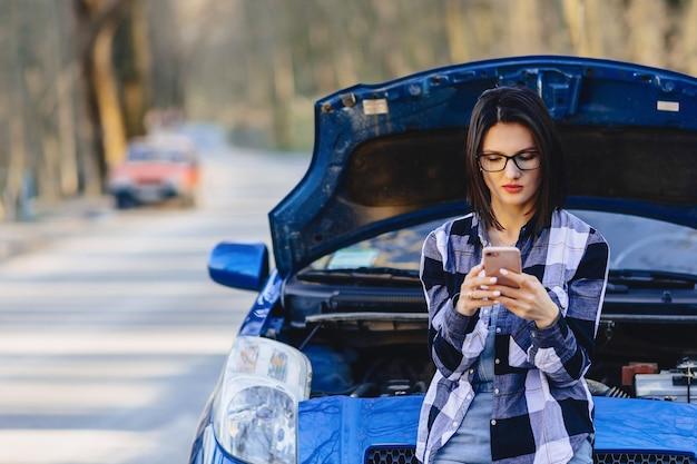Garota atraente com telefone perto de capô aberto do carro Foto Premium