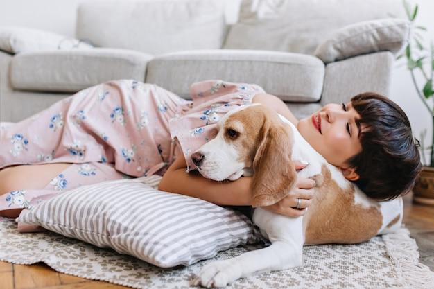 Garota atraente com uma expressão facial feliz deitada no carpete perto de um cachorro beagle com orelhas castanhas Foto gratuita
